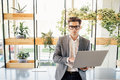 Happy freelance business man sitting on office desk with laptop in hands and typing, looking at camera Royalty Free Stock Photo