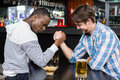 Happy friend arm wrestling each other in a bar Stock Images