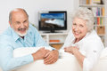 Happy friendly elderly couple relaxing in their living room in front of the television turning to smile at the camera Stock Images