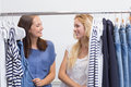 Happy friends browsing in the clothes rack two Royalty Free Stock Image