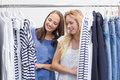 Happy friends browsing in the clothes rack two Royalty Free Stock Photos