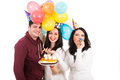 Happy friends celebrate woman birthday three at women with cake and balloons blow out horn party isolated on white background Royalty Free Stock Photos