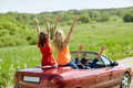 Happy friends driving in cabriolet car at country Royalty Free Stock Photo
