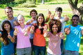 Happy friends gesturing thumbs up group portrait of at college campus Stock Photo
