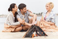 Happy friends having fun around bonfire three sitting under blanket and warming near fire Stock Image