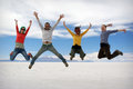 Happy friends jumping outdoor a group of young in solar de uyuni bolivia Royalty Free Stock Photography
