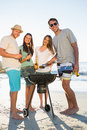 Happy friends looking at camera while having barbecue together on the beach Royalty Free Stock Image
