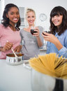 Happy friends making spaghetti dinner together and drinking red wine smiling at camera in kitchen Royalty Free Stock Photo