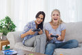 Happy friends playing video games and having fun at home on the couch Royalty Free Stock Image