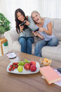 Happy friends playing video games and laughing at home on the couch Stock Photography