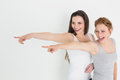 Happy friends pointing away against white background two young female Stock Image
