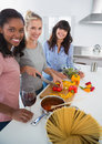 Happy friends preparing a meal together looking at camera home in kitchen Royalty Free Stock Image