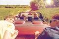 Happy friends pushing broken cabriolet car Royalty Free Stock Photo