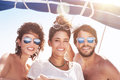 Happy friends on sailboat portrait of three people having fun best traveling together enjoying bright sunny summer days in sea Stock Photography