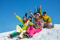 Happy friends on snowboard resort men and women sit in snow with snowboards lifting and waving hands Stock Photography