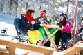 Happy friends spending time together and drink after skiing in c Royalty Free Stock Photo