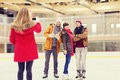 Happy friends taking photo on skating rink Royalty Free Stock Photo