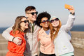 Happy friends taking selfie by smartphone outdoors