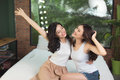 Happy friends or teenage girls having fun and jumping on bed at Royalty Free Stock Photo