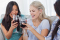 Happy friends toasting with red wine together at home on couch Stock Photos