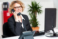 Happy front desk lady attending clients call Royalty Free Stock Photo