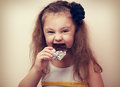 Happy fun smiling kid girl biting dark chocolate with craving ey