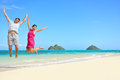 Happy fun tourists couple jumping beach vacation hawaii young cheering for summer holidays showing success happiness and joy on Stock Photo