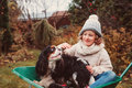 Happy funny child girl riding her dog in wheelbarrow in autumn garden, candid outdoor capture