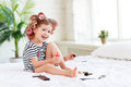 Happy funny child girl with hair curlers does a pedicure, paints Royalty Free Stock Photo