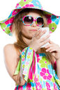 Happy funny little girl in summer colorful dress and sunglasses smiling and holding mobile phone isolated on white background Royalty Free Stock Images