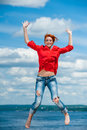 Happy funny young redhead woman jumps beautiful with laugh under blue cloudy sky concept of leisure and recreation Royalty Free Stock Photos