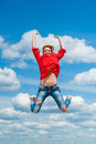 Happy funny young redhead woman jumps laughing beautiful with laugh under blue cloudy sky concept of leisure freedom happiness Royalty Free Stock Image