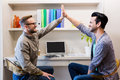 Happy gay couple doing high five in office Royalty Free Stock Image