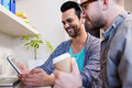 Happy gay couple using tablet at home Royalty Free Stock Image
