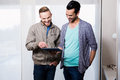 Happy gay couple using tablet at home Royalty Free Stock Images