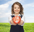 Happy girl with alarm clock over summer background Royalty Free Stock Photo