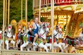 Happy girl in an amusement park rides a horse on a carousel in the summer Royalty Free Stock Photo