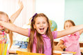 Happy girl with arms apart laughs during lesson super laughing happily in school and other girls behind her Royalty Free Stock Photo