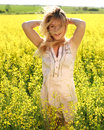 Happy girl with arms up relaxing in the spring yellow field at sunset Royalty Free Stock Photo