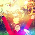 Happy girl in autumn the sun with leaves Stock Photos