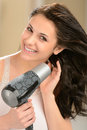 Happy girl blow drying her hair with dryer Royalty Free Stock Photo