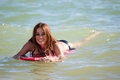 Happy girl on a body board cute brunette surfing and smiling Royalty Free Stock Photo