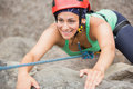 Happy girl climbing rock face wearing red helmet Stock Images
