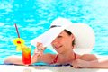 Happy girl with a cocktail at the pool holding hat hand Royalty Free Stock Images