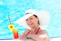 Happy girl with cocktail relaxing by the pool young Royalty Free Stock Photos