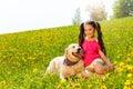 Happy girl cuddling dog sitting on the grass