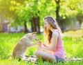 Happy girl and dog having fun in summer sunny park Stock Photos