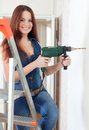 Happy girl drills hole in wall the with drill Royalty Free Stock Photography