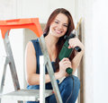 Happy girl in dungarees with drill on stepladder Stock Photography