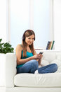 Happy girl enjoying music on mp player beautiful brunette sitting sofa at home Stock Photo